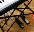 View of the M-Audio SP2 sustain pedal on the floor next to the Yamaha FC4 pedal.