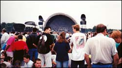 A crowd of people at the Pink Floyd concert, mid afternoon, overcast sky. The stage can be seen in the distance.