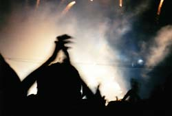 Bright lights and smoke coming from the Pink Floyd stage, with the silouette of someone in the crowd in the foreground, hands raised above their head.