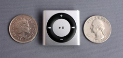 The iPod Shuffle between a UK 10p coin and an American quarter.