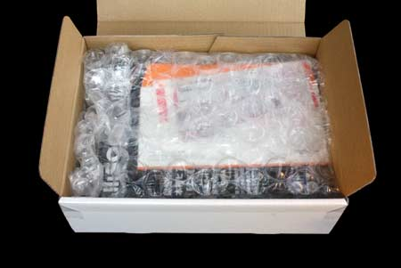A box opened, showing bubblewrap inside. A pamphlet and a delivery note can be seen through the bubble wrap.